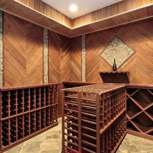 Klassisk inredning av en mellanstor vinkällare, med klinkergolv i keramik, vindisplay och rosa golv
