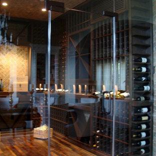 Wine cellar - mid-sized contemporary medium tone wood floor wine cellar idea in Orange County with display racks