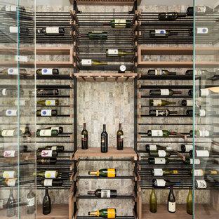 Imagen de bodega contemporánea, pequeña, con suelo de madera en tonos medios, vitrinas expositoras y suelo gris