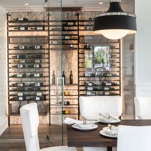 Exempel på en liten modern vinkällare, med mellanmörkt trägolv, vindisplay och grått golv