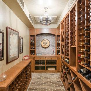Inspiration för stora rustika vinkällare, med tegelgolv, vinställ med diagonal vinförvaring och brunt golv