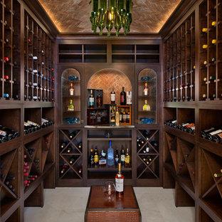 Réalisation d'une très grand cave à vin méditerranéenne avec un sol en marbre, des casiers et un sol beige.