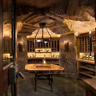 Rustik inredning av en mycket stor vinkällare, med skiffergolv, vindisplay och grått golv