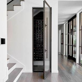 Idée de décoration pour une petit cave à vin design avec un sol en bois foncé, des casiers et un sol marron.