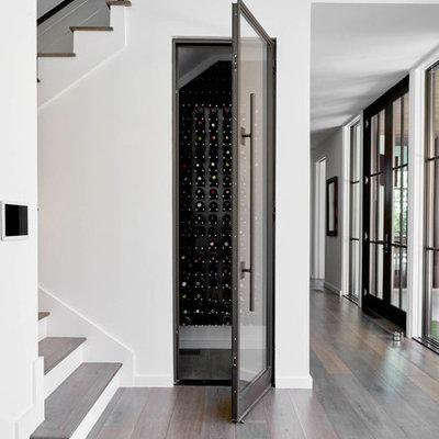 Small trendy dark wood floor and brown floor wine cellar photo in Dallas with storage racks
