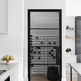 Idee per una grande cantina design con pavimento in legno massello medio, rastrelliere portabottiglie e pavimento marrone