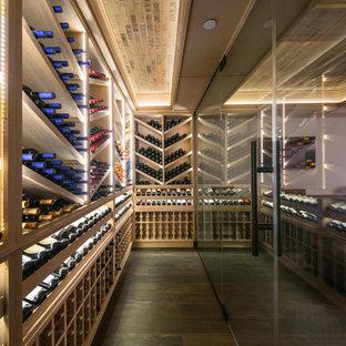 Idée de décoration pour une grand cave à vin tradition avec un sol en carrelage de porcelaine, un présentoir et un sol marron.