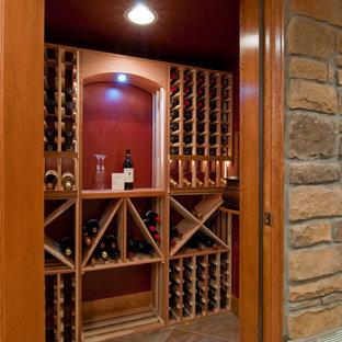 Aménagement d'une très grand cave à vin montagne avec moquette et des casiers losange.