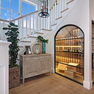 Inspiration för maritima vinkällare, med mellanmörkt trägolv, vinhyllor och gult golv