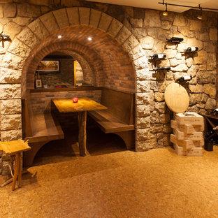 Exemple d'une grand cave à vin montagne avec un sol en liège, des casiers et un sol marron.