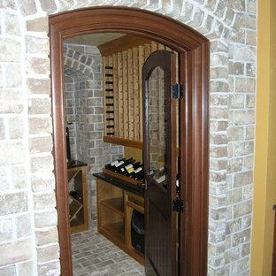 Ejemplo de bodega tradicional, de tamaño medio, con suelo de ladrillo, botelleros y suelo gris
