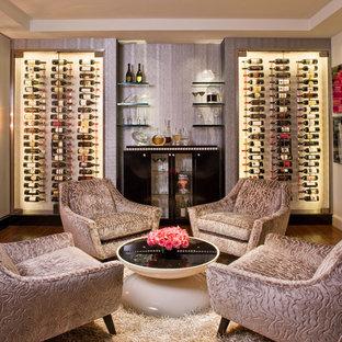 Bild på en stor funkis vinkällare, med mörkt trägolv, vinhyllor och brunt golv
