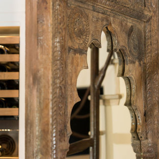 Wine cellar - small eclectic travertine floor and beige floor wine cellar idea in Los Angeles