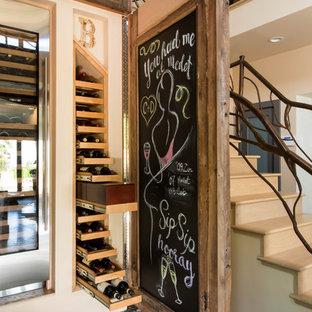 Exempel på en stor eklektisk vinkällare, med travertin golv och vinhyllor