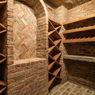 Idéer för en stor klassisk vinkällare, med tegelgolv och vinställ med diagonal vinförvaring