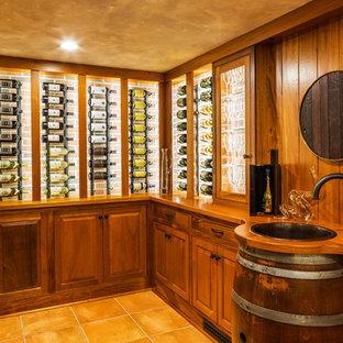 Klassisk inredning av en mellanstor vinkällare, med vinhyllor, klinkergolv i terrakotta och beiget golv