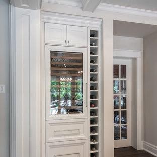 Ejemplo de bodega contemporánea con suelo de madera en tonos medios y botelleros