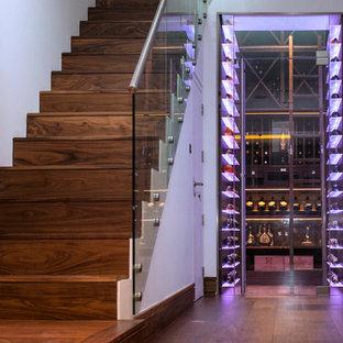 Cette image montre une petit cave à vin design avec un sol en bois foncé et un sol marron.