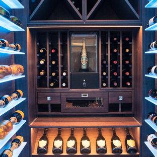 Aménagement d'une petite cave à vin contemporaine avec un sol en bois foncé et un sol marron.