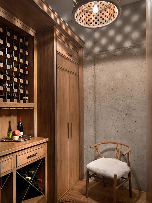 wine lighting. inspiration for a rustic light wood floor and beige wine cellar remodel in denver with lighting o