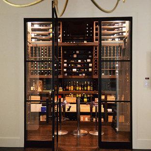 Cette image montre une cave à vin traditionnelle de taille moyenne avec des casiers, un sol en bois foncé et un sol marron.