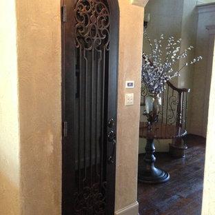Mid-sized elegant medium tone wood floor wine cellar photo in Dallas with storage racks