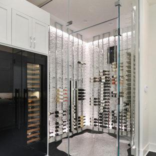 Idée de décoration pour une cave à vin minimaliste de taille moyenne avec un sol en bois foncé, des casiers et un sol noir.