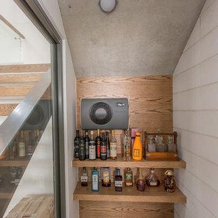 Immagine di una piccola cantina design con pavimento in cemento e portabottiglie a vista