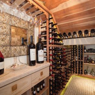 フェニックスの中サイズの地中海スタイルのおしゃれなワインセラー (トラバーチンの床、ワインラック) の写真