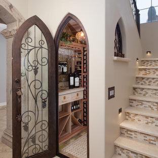 Exemple d'une cave à vin méditerranéenne de taille moyenne avec un sol en travertin et des casiers.