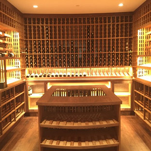 Design ideas for an expansive contemporary wine cellar in Los Angeles with light hardwood flooring, storage racks and brown floors.