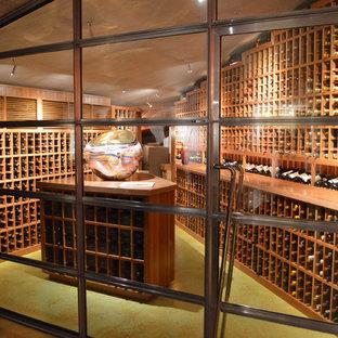 Idée de décoration pour une grand cave à vin design avec béton au sol, des casiers et un sol vert.