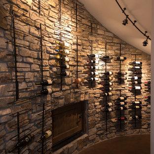 デンバーの大きいサンタフェスタイルのおしゃれなワインセラー (コンクリートの床、ディスプレイラック、茶色い床) の写真