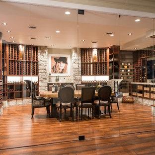 Imagen de bodega clásica, grande, con suelo de madera en tonos medios y botelleros