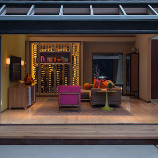 Diseño de bodega ecléctica con suelo de madera clara y vitrinas expositoras