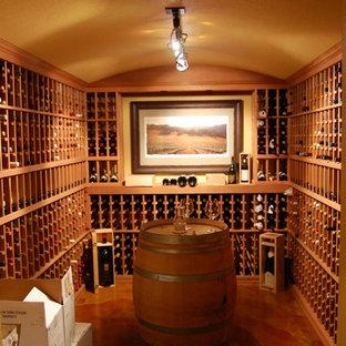 Inspiration för stora klassiska vinkällare, med betonggolv, vinhyllor och orange golv