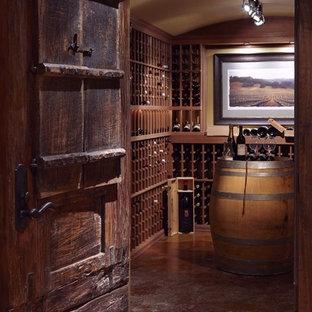 Exempel på en stor klassisk vinkällare, med betonggolv, vinhyllor och orange golv