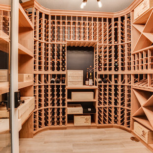 Inspiration for an expansive farmhouse wine cellar in Minneapolis with light hardwood flooring, storage racks and beige floors.