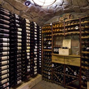Cette photo montre une grand cave à vin montagne avec béton au sol, des casiers et un sol marron.