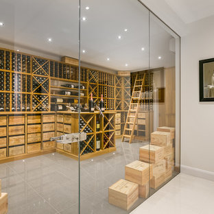 Inspiration for an expansive contemporary wine cellar in London with porcelain flooring, storage racks and grey floors.