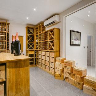 Foto de bodega minimalista, extra grande, con suelo de baldosas de porcelana, botelleros y suelo gris