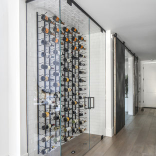Réalisation d'une cave à vin design avec un sol en bois brun, des casiers et un sol gris.