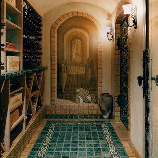 Foto de bodega mediterránea, de tamaño medio, con suelo de baldosas de terracota y botelleros