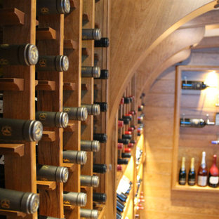 Photo of a medium sized nautical wine cellar in Chicago with light hardwood flooring, display racks and brown floors.
