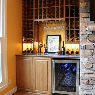 Inspiration för små klassiska vinkällare, med ljust trägolv och vinhyllor