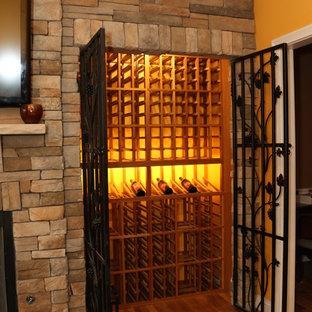 Exemple d'une petit cave à vin chic avec un sol en bois brun et des casiers.