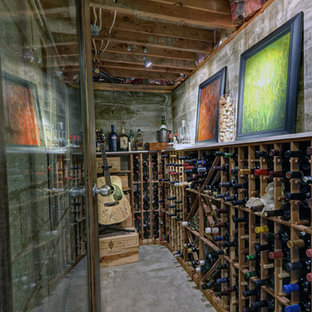 Example of a small eclectic concrete floor wine cellar design in Other with storage racks