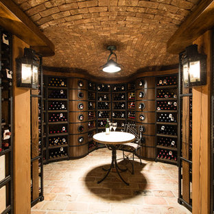 Example of a small tuscan brick floor and pink floor wine cellar design in Charleston with storage racks