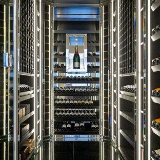 Inspiration pour une cave à vin design avec des casiers et un sol noir.