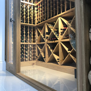 This is an example of a medium sized modern wine cellar in Other with porcelain flooring, storage racks and beige floors.